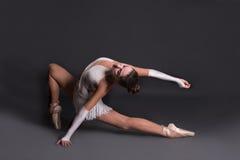 Den unga ballerina i vita pointesdanser royaltyfri bild