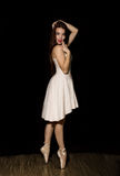 Den unga ballerina med en perfekt kropp dansar i pointeskor på mörk bakgrund Royaltyfri Fotografi
