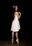 Den unga ballerina med en perfekt kropp dansar i pointeskor på mörk bakgrund Fotografering för Bildbyråer