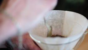 Den unga baristagrabben förbereder en puroisePurower kemex Han häller varmt kaffevatten från en metallkokkärl, som hälls stock video