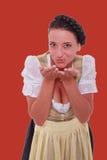 Den unga bayerska kvinnan i dirndlen som andas på, gömma i handflatan av dina händer Fotografering för Bildbyråer