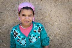 Den unga Berberflickan poserar framme av henne hem i en liten Berberby i den Ziz dalen, nära Errachidia, Marocko royaltyfri bild