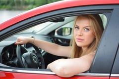 Den unga blåögda blondinen ser till och med bilfönstret royaltyfri fotografi