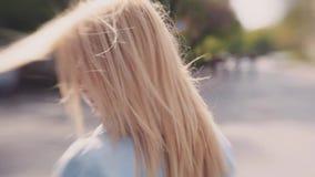 Den unga blonda attraktiva flickan i jeans klår upp att undra ner gatorna, blåsväder Vinkande hår, gulligt leende arkivfilmer