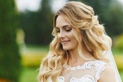 Den unga blonda bruden med ett härligt leende och med den stilfulla gifta sig frisyren snör åt in vit klänningdet fria i morgonen fotografering för bildbyråer