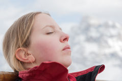 Den unga blonda Caucasian blonda kvinnaflickan som solbadar berget, skidar slutet för framsidan för snöhimmelberget Arkivfoton