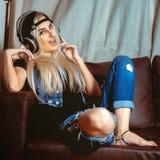 Den unga blonda flickan i jeans beklär att lyssna till musiken i hea Arkivbild