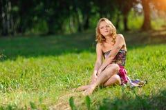 Den unga blonda flickan i den ljusa färgrika klänningen som poserar att ligga på gräs i sommar, parkerar i strålarna av den ljusa Royaltyfri Fotografi