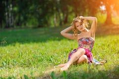 Den unga blonda flickan i den ljusa färgrika klänningen som poserar att ligga på gräs i sommar, parkerar i strålarna av den ljusa Arkivbild