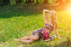 Den unga blonda flickan i den ljusa färgrika klänningen som poserar att ligga på gräs i sommar, parkerar i strålarna av den ljusa Arkivfoto