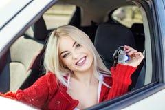 Den unga blonda flickan köper en bil Begreppstur, livsstil, chaufför, a royaltyfri foto