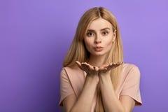 Den unga blonda flickan med gömma i handflatan av hennes bröstkorg uttrycker framme hennes känsla royaltyfri fotografi