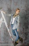 Den unga blonda flickan med kort hår i ett grov bomullstvillomslag och jeans sitter och ser Royaltyfri Foto