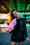 Den unga blonda kvinnan äter sockervaddfloss fotografering för bildbyråer