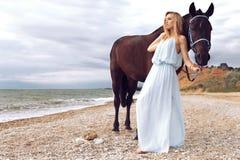 Den unga blonda kvinnan bär den eleganta klänningen som poserar med den svarta hästen Arkivfoton