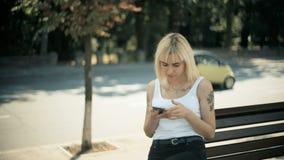 Den unga blonda kvinnan går i stad sitter ner på bänken läser meddelandet i smartphonen tyst stock video