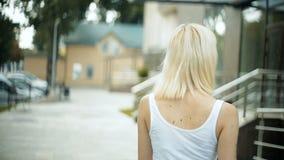 Den unga blonda kvinnan går runt om stadssorten av slakt som spårar modellblickarna runt om leenden arkivfilmer