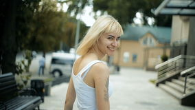 Den unga blonda kvinnan går runt om stadssorten av slakt som spårar modellblickarna runt om leenden stock video