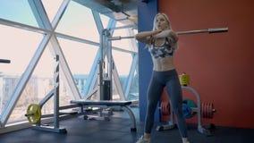 Den unga blonda kvinnan gör skivstångsquats i modermidrottshall med det stora fönstret arkivfilmer
