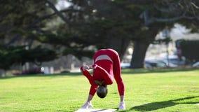 Den unga blonda kvinnan i röd latexdräkt gör yogaövningar stock video
