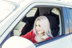 Den unga blonda kvinnan kör en bil Begreppstur, livsstil, chaufför royaltyfri foto