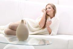 Den unga blonda kvinnan med buteljerar av doft Royaltyfri Fotografi