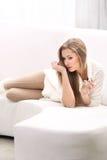Den unga blonda kvinnan med buteljerar av doft Fotografering för Bildbyråer