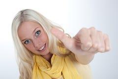 Den unga blonda kvinnan med tum göra en gest upp royaltyfri foto