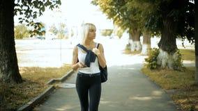 Den unga blonda kvinnan promenerar gränden, mellan de lugna träden, blickar omkring lager videofilmer
