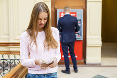Den unga blonda kvinnan rymmer kontanta dollar royaltyfri bild