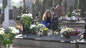 Den unga blonda kvinnan satte stearinljuset p? grav efter makefaderf?rlust i kyrkog?rd 4K arkivfilmer
