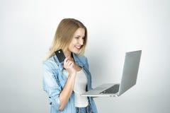 Den unga blonda kvinnan ser lycklig rymma hennes kontokort i en hand och bärbar dator i andra och direktanslutet att shoppa, isol arkivbild