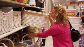 Den unga blonda kvinnan shoppar in hållande ögonen på korgar stock video