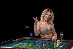 Den unga blonda kvinnan som bär den härliga sexiga skinande klänningen, spelar rouletten i kasinot Arkivbild