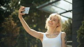 Den unga blonda kvinnan som gör ett selfiefoto som ler, uttrycker en olik sinnesrörelse lager videofilmer