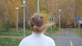 Den unga blonda kvinnan som kör i hösten, parkerar stock video