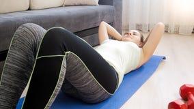 Den unga blonda kvinnan som ligger på mattt hemmastatt för kondition och gör, sitter ups Royaltyfria Foton