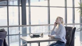 Den unga blonda kvinnan talar på telefonen i den stilfulla restaurangen, ultrarapid lager videofilmer