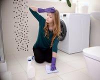 Den unga blonda kvinnan tvättar golvet i badrummet Arkivfoton