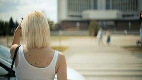 Den unga blonda kvinnan väntar på bilar för att passera att gå att korsa vägröda ljuset korsa tillbaka sikt arkivfilmer