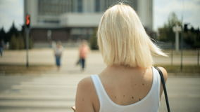 Den unga blonda kvinnan väntar på bilar för att passera att gå att korsa vägröda ljuset korsa tillbaka sikt stock video
