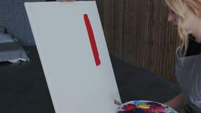 Den unga blonda kvinnliga konstnären i förklädet tar den röda målarfärgen från paletten och gör på det första suddet med en spate stock illustrationer