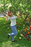 Den unga blondinen med ett stort br?st st?r i parkerar under ett blomma tr?d arkivbilder