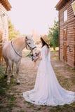 Den unga bohostilbruden slår den vita hästen royaltyfria bilder