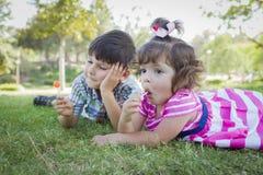Den unga brodern och behandla som ett barn systern Enjoying Their Lollipops utomhus fotografering för bildbyråer