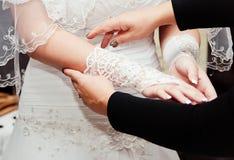 Den unga bruden klär handskar Arkivfoto