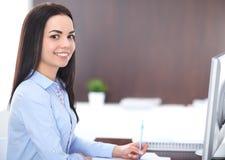 Den unga brunettaffärskvinnan ser som en studentflicka som i regeringsställning arbetar Latinamerikan eller latin - amerikansk fl arkivfoton