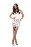 Den unga brunetten garvade skönhet i akimbo poserar att se ner Royaltyfri Fotografi