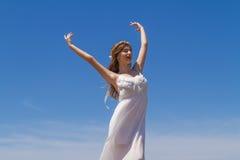 Den unga brunetten i den vita bräckliga klänningen tycker om Arkivbild