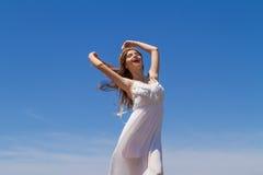 Den unga brunetten i den vita bräckliga klänningen tycker om Royaltyfria Foton